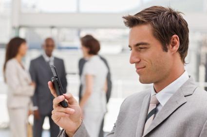 Closeup of young businessman text messaging